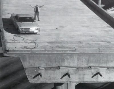 Courtesy Ray Spallone. Former San Jose city councilman Joe Colla as he appeared in 1976, when he paid to have a car lifted by helicopter atop the not-yet-completed flyover interchange between U.S. 101 and Interstates 280 and 680. Construction of the interchange had been halted by then-Governor Jerry Brown in 1975. Colla's stunt prompted the Legislature to approve funding to complete the interchange . There is a resolution in the Legislature to rename the interchange in Colla's honor.